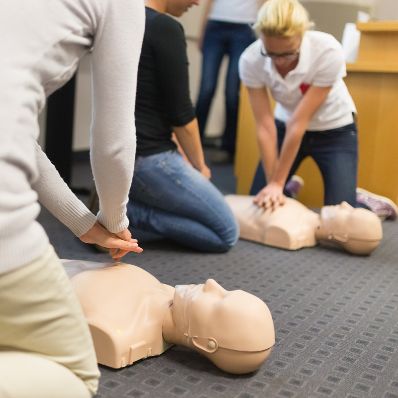 A group of adult education students practitcing CPR chest compressioon on a dummy.