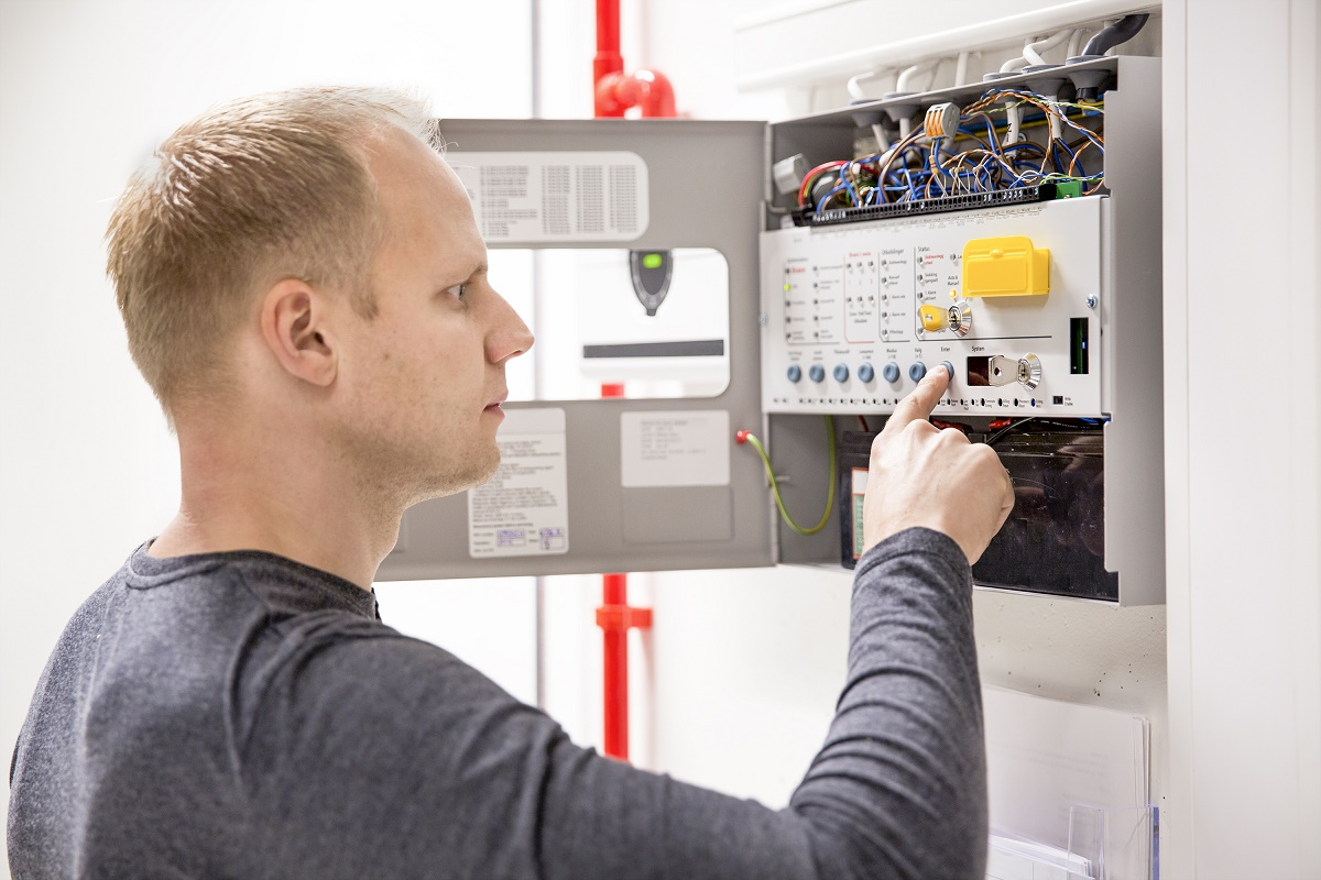 IT engineer or technician looking at alarm panel for aspirating fire detection system in datacenter. Inerte gass or nuvek gass system.